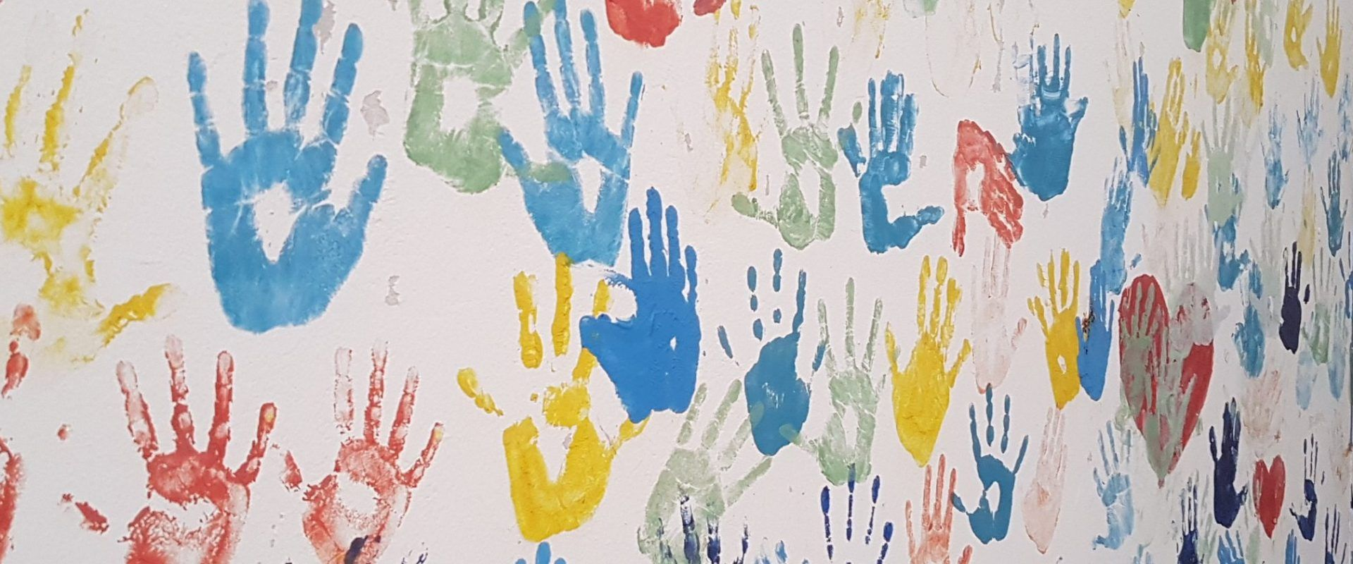Multi-coloured handprints on a wall.