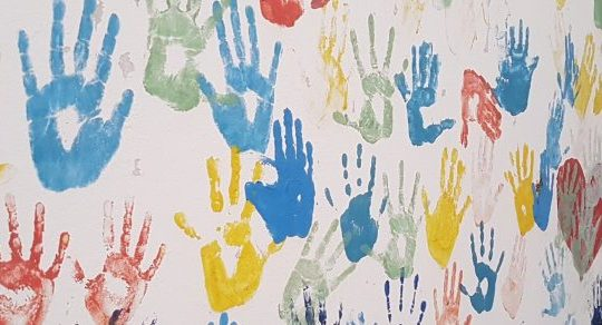 Multi-coloured handprints on a wall