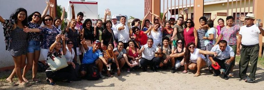 A group of Peruvians wave and smile outside a school.