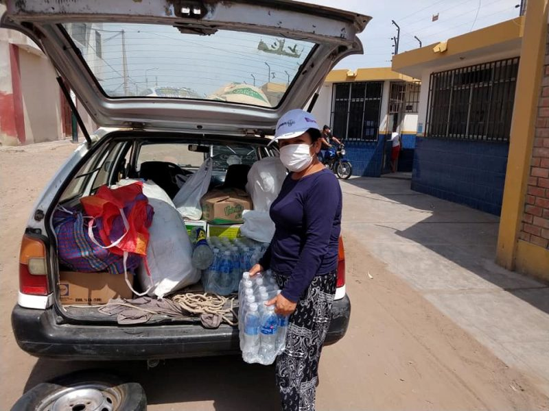 Flor Reaño delivers emergency supplies from the back of a car.
