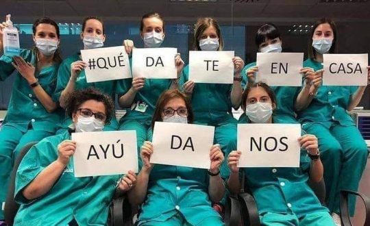 "hospital workers in masks hold signs that say ""help us by staying at home"""