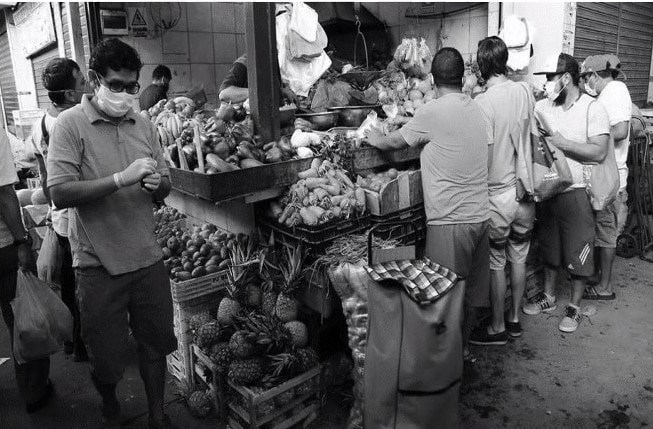 Men at a street market shopping for food.
