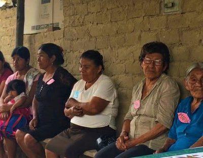 rural women sitting on benches in San Isidro