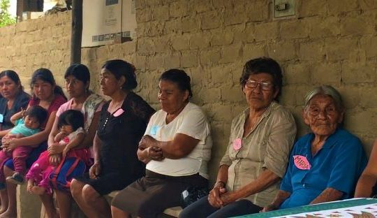 rural women sitting on benches in San Isidro