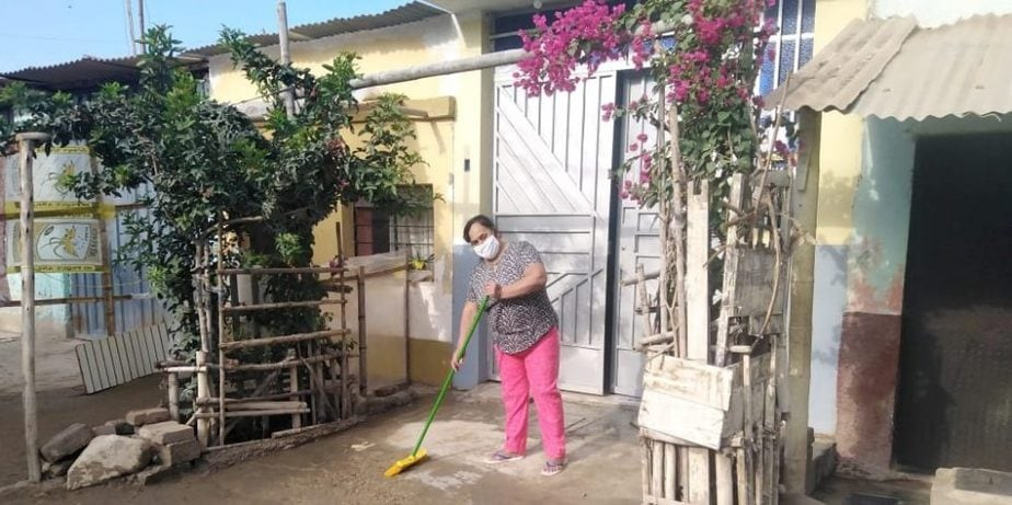 Woman in mask sweeping entrance to her home.