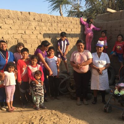 Mothers and children stand in front of an adobe wall