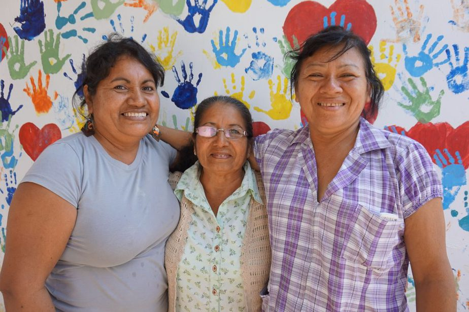 Three women against a colourful wall covered in hearts and handprints.