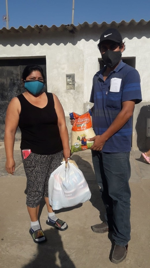 Man in mask delivering food to woman in mask.