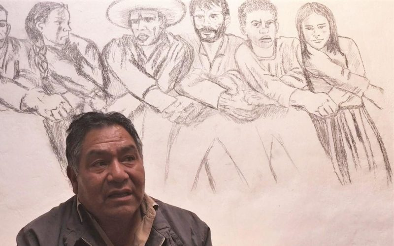 Man sits in front of mural showing campesinos with joined hands
