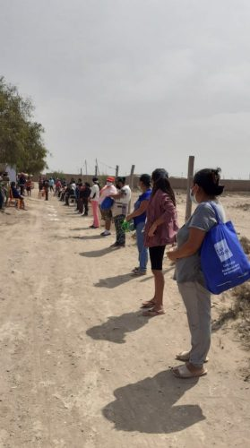 women wait in line for food aid