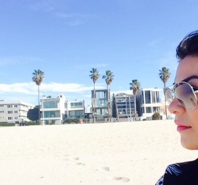 woman in profile with beach, hotels and palm trees in the background