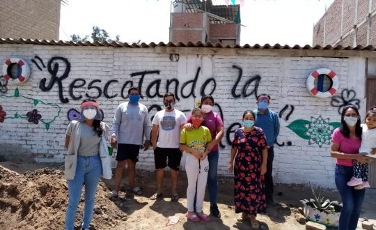 people with spades and plants stand in front of walls that says rescuing our street