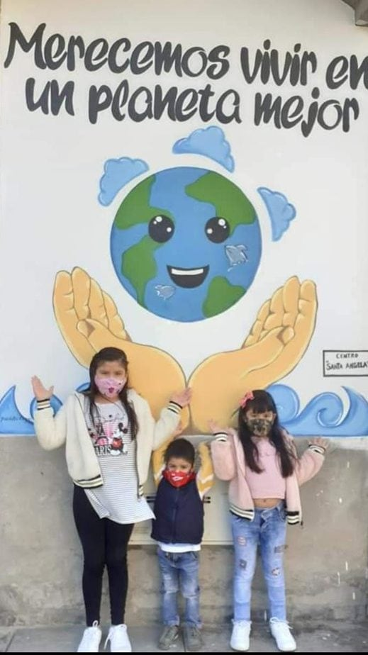 three children stand in front of a wall that says we deserve to live in a better world