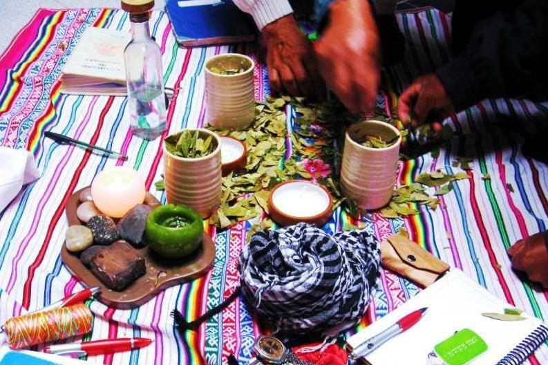 ceremony showing candles, coca leaves and a notebook on a woven cloth