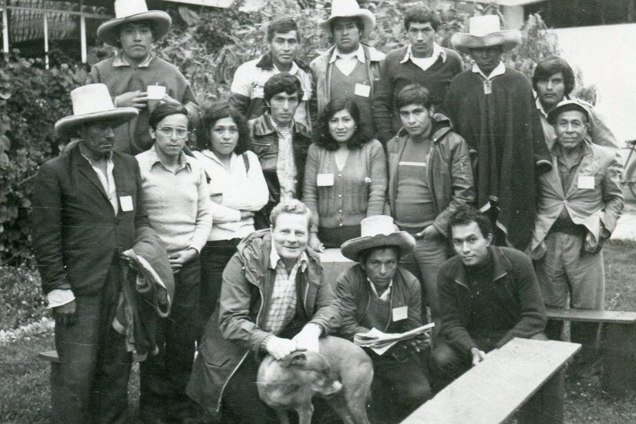 A group of rural Peruvian stand behind Father John Medcalf