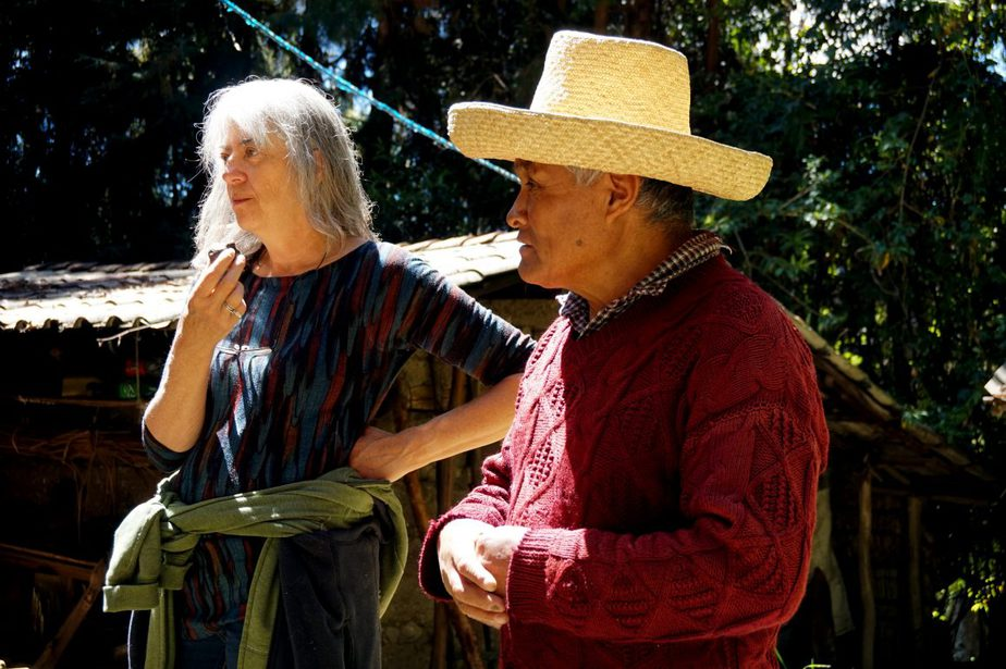 Peruvian man in wide brimmed hat stands next to Canadian women with sweater tied at waist in front of house with corrugated roof