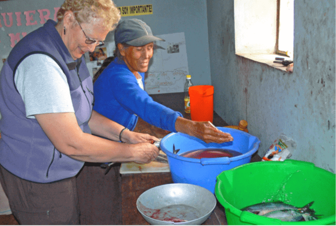 Two women stand over plastic bowls containing fish to be fried