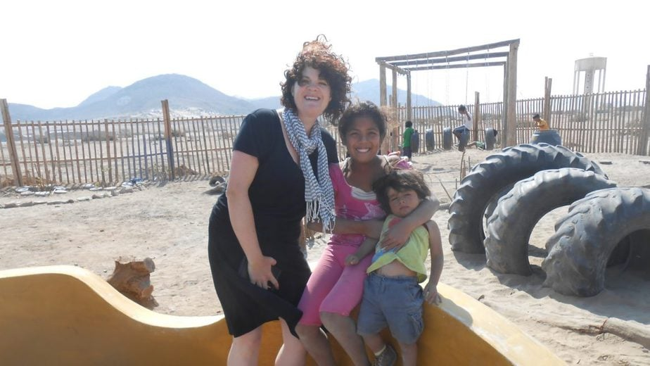 woman and two children stand together in playground in Peru