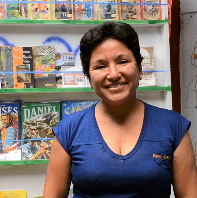 Flor stands in front of stand of books smiling