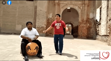 Man recites poem while another man drums on checo in from of Zaña ruins