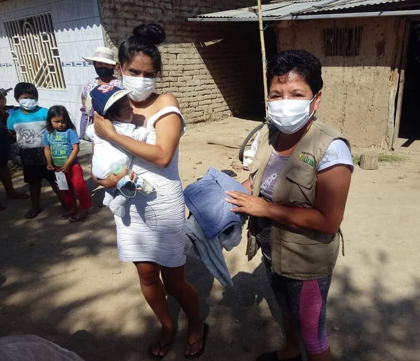 Woman in mask delivering clothes to young woman with baby