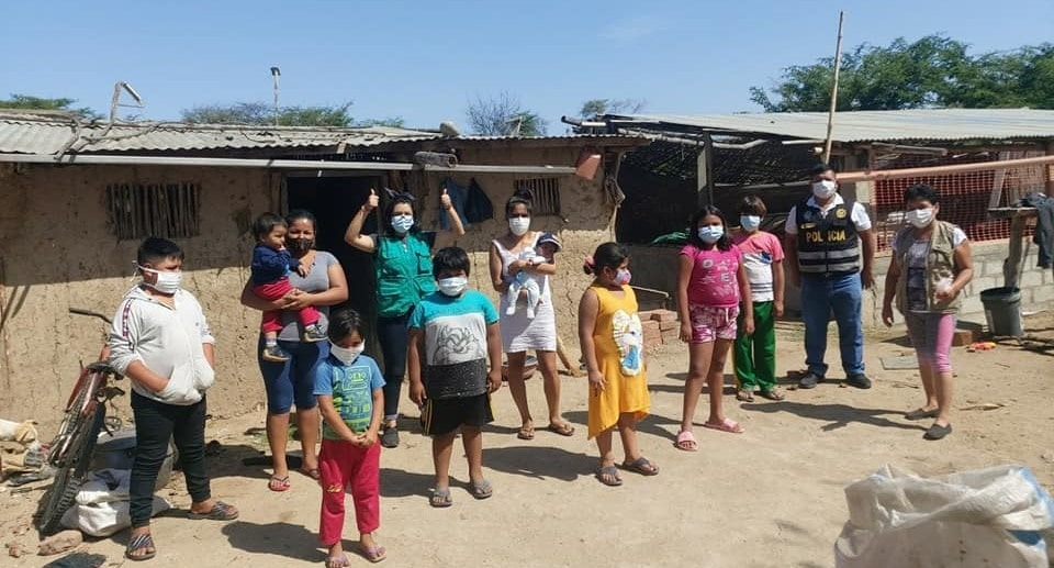 adults and children in masks wave from in front of very humble home