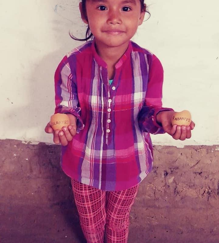 little girl holds egg shells filled with seedlings